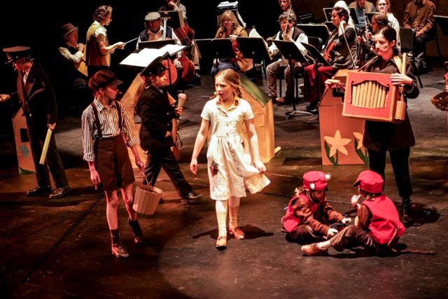 A photo of HTYP's production of Brundibár: A Children's Opera featuring a girl on sttage with braids and a light coloured dress standing next to a boy in a cap, shorts, and suspenders, next to an adult with a cardboard device and two children in red caps and vests sitting on the ground. In the background is a symphony.